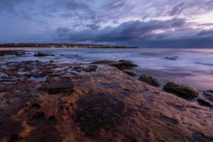 Seascape sunrise long exposure with flowing water and violet sky