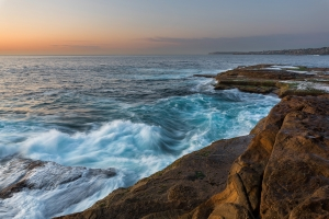 Sunrise seascape with unrest sea and blue water and with sky lit orange rocks