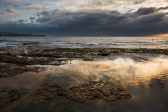 Seascape sunrise long exposure with calm water puddle and grim sky