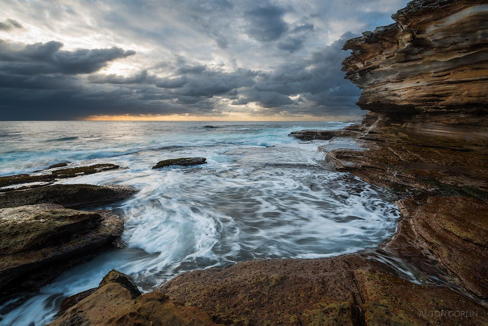 Magic Point seascape sunrise with unrest sea and grim sky and cliffs